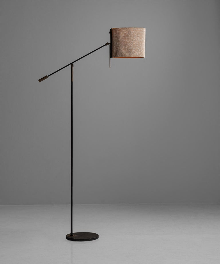 """Black lacquered & gilt brass floor lampby Maison Lunel, France, circa 1950  Black lacquered cast iron base, with metal arm, brass hinge, handles and solid brass counterweight.  Measures: 11.5"""" W x 30"""" D x 75"""" H."""