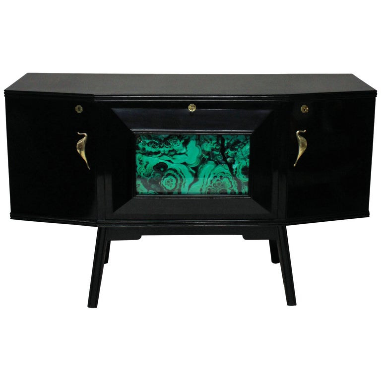A stylish Italian bar credenza of interesting angular design in black lacquer with sepele wood interior, with brass hardware and a faux malachite central panel and mirrored interior.