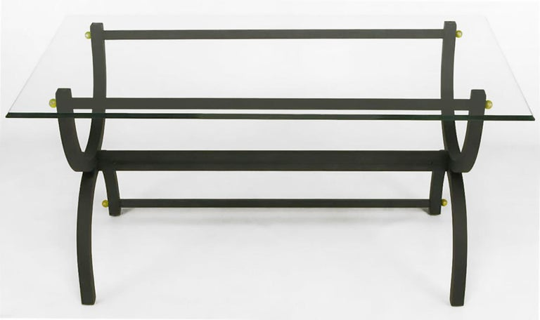 Matte black lacquered steel curule form writing table, with lower back stretcher and multiple brass ball details. Triple beveled ogee edge glass top is one-half inch thick. With a narrower glass top, would also function as a console or sofa table.