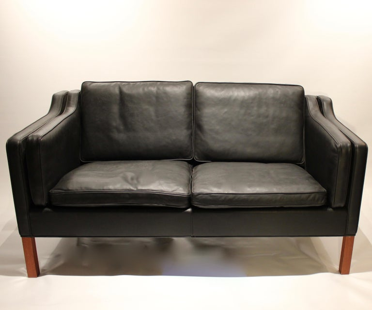 Black leather 2-seat sofa with legs of mahogany, model 2212, designed by Børge Mogensen in 1962 and manufactured by Fredericia furniture in the 1980s. The sofa is in great vintage condition and we currently have two in stock.