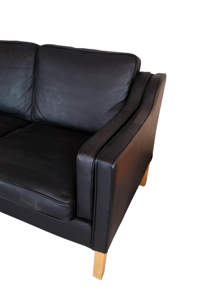 Black leather 2 seater sofa with legs of oak, manufactured by Stouby Furniture in the 1960s. The sofa is in great vintage condition.