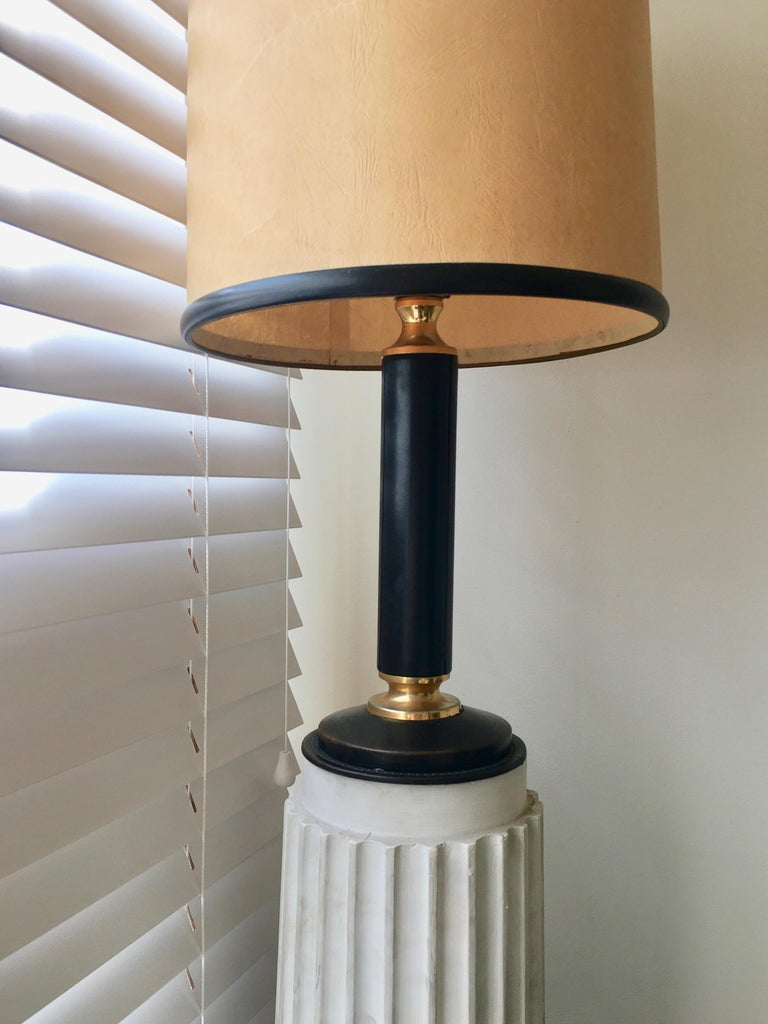 Elegant black leather lamp with brass rings. Original shade with black leather straps on top and bottom. One light. By J.Adnet, France 1950.
