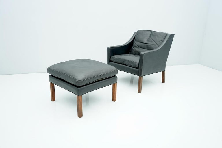 Black leather lounge chair with stool by Børge Mogensen, Denmark, 1960s  Measurements: Chair W 70 cm (27.5 in), D 81 cm (31.9 in.), H 78.5 cm. (31 in.) Stool, W 64 cm (25.2 in), D 62 cm (24.4 in.), H 40 cm (15.7 in)  Good condition.