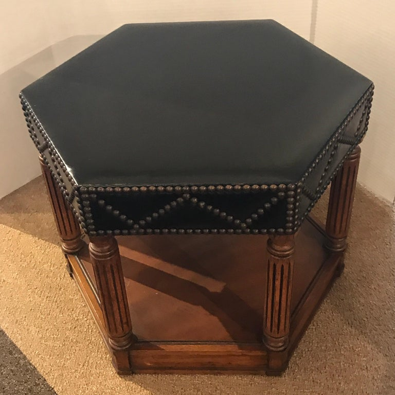 Black leather nailhead stool in the manner of Maison Jansen, with hexagonal black leather top, with continuous brass nailheads. Raised on reeded columns, on a plinth base.