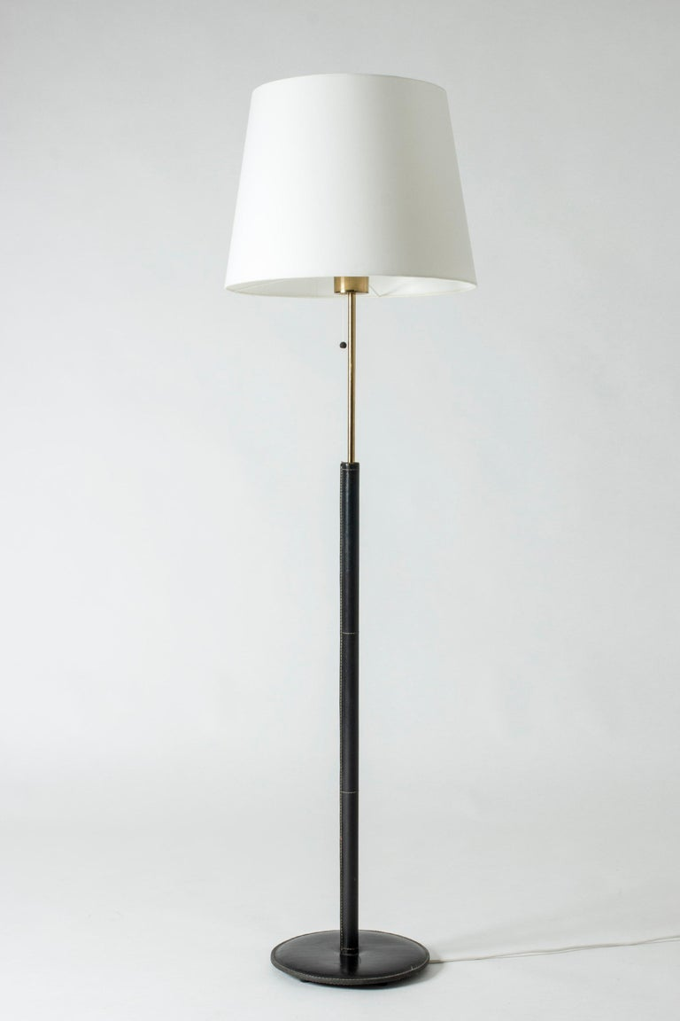 Cool floor lamp from Bergboms with a leather-clad brass pole and foot. Black leather with contrasting white seams.  Bergboms was a successful Swedish lighting firm which manufactured both own designs and those of international designers such as