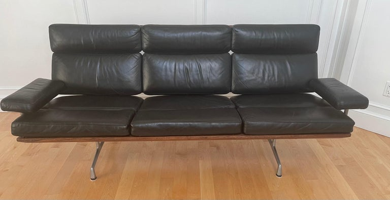 Authentic black leather and walnut three seat sofa by Charles & Ray Eames for Herman Miller, circa 1980s. The sofa is in excellent vintage condition and features solid wood back and frame panels finished with gunstock oil, polished aluminum legs and