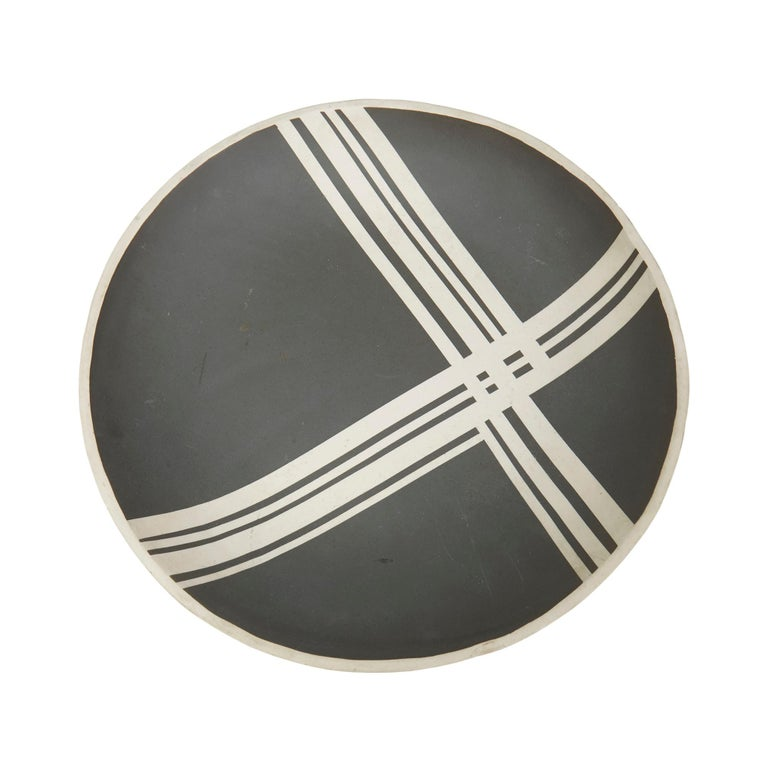 A striking and large studio pottery bowl decorated with a interwoven linear pattern in cream against a black ground. The shaped rounded bowl is finished in matt glaze and has an incised AV monogram to the base.  Incised AV monogram to the base.