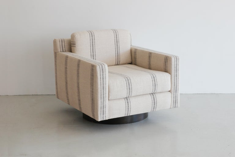 Fantastic pair of newly produced square swivel chairs in the style of Milo Baughman. Comfortable cushioned seats with low profile back cushion. Sits on walnut wood swivel base. Newly upholstered in black striped natural linen. Great modern design
