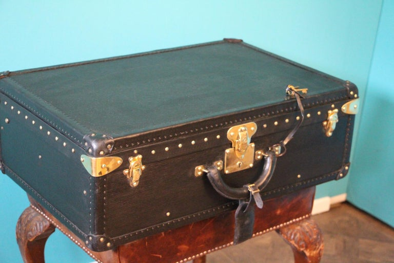 This top of the range all black leather Alzer 65 rigid suitcase features black leather trim, all solid brass LV stamped lock, clasps and studs. Large leather handle. 1 matching black epi leather name holder. Its interior is in excellent condition,