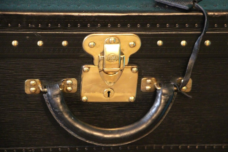 This top of the range all black leather Alzer 80 rigid suitcase features black leather trim, all solid brass LV stamped lock, clasps and studs. Large leather handle. 2 keys. Its interior is in excellent condition, as new. It is lined in grey suede,