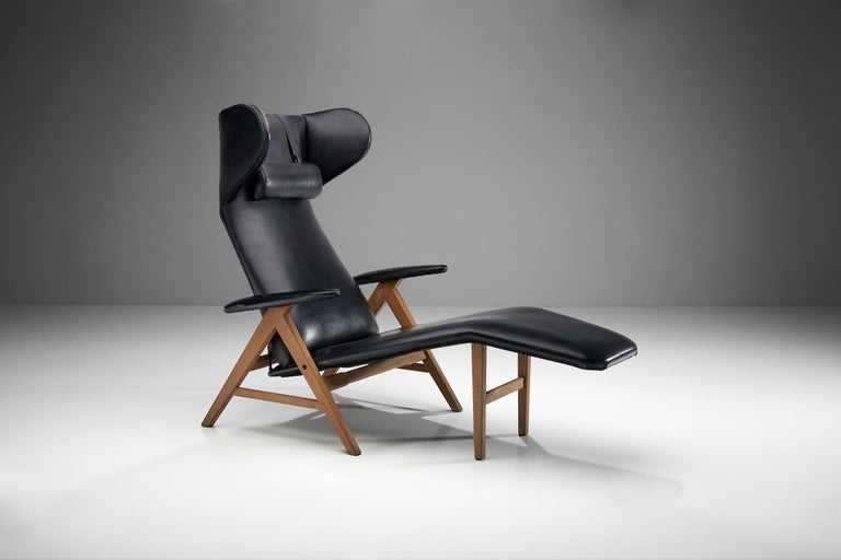 Black chaise longue with stained beech frame, commonly attributed to H.W. Klein for Bramin.   This wonderfully crafted lounge chair has a tilt function, which makes it extremely comfortable. The seat is extended in soft lines as a chaise longue to