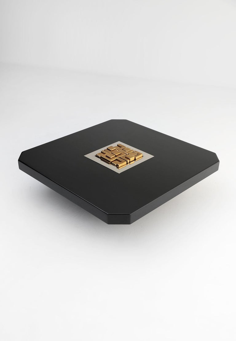 Black lacquered coffee table by Lova Creation, Belgium. This decorative coffee table is signed and numbered 'Lova Creation 1985, 19/50'. The table stands in a very good condition and has a variable artwork in the center. Different figures in brass
