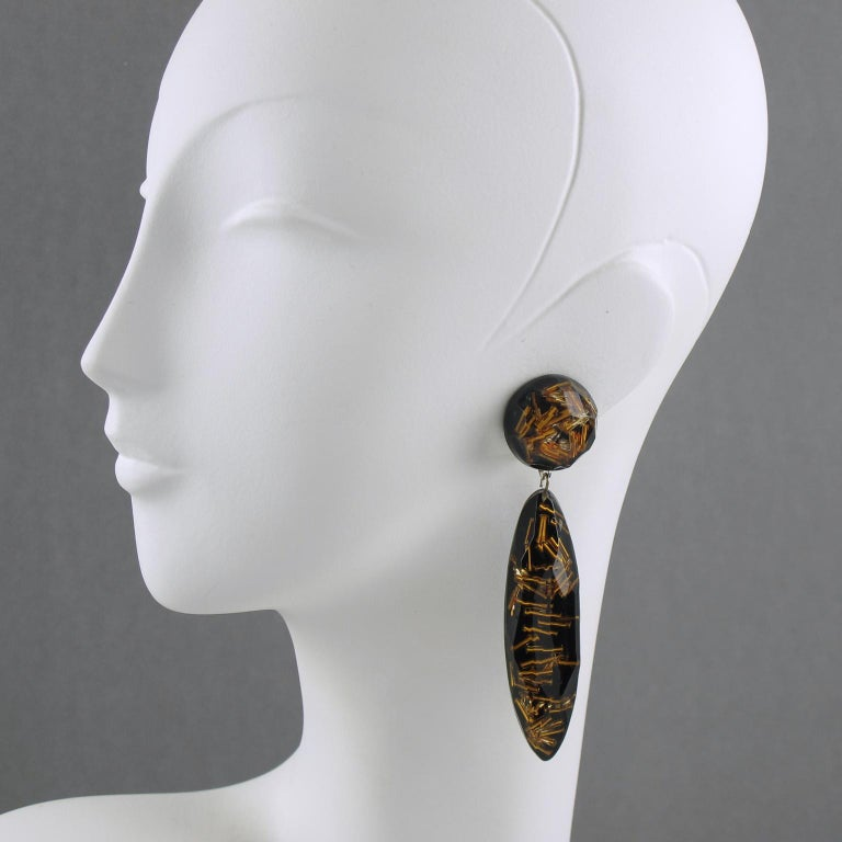 Lovely French oversized Lucite clip-on earrings. Featuring dangling shape, with an extra-long drop carved and faceted bead, compliment with gilt stick beads inclusions over black background. No visible maker's mark. Measurements: 3.94 in. long (10