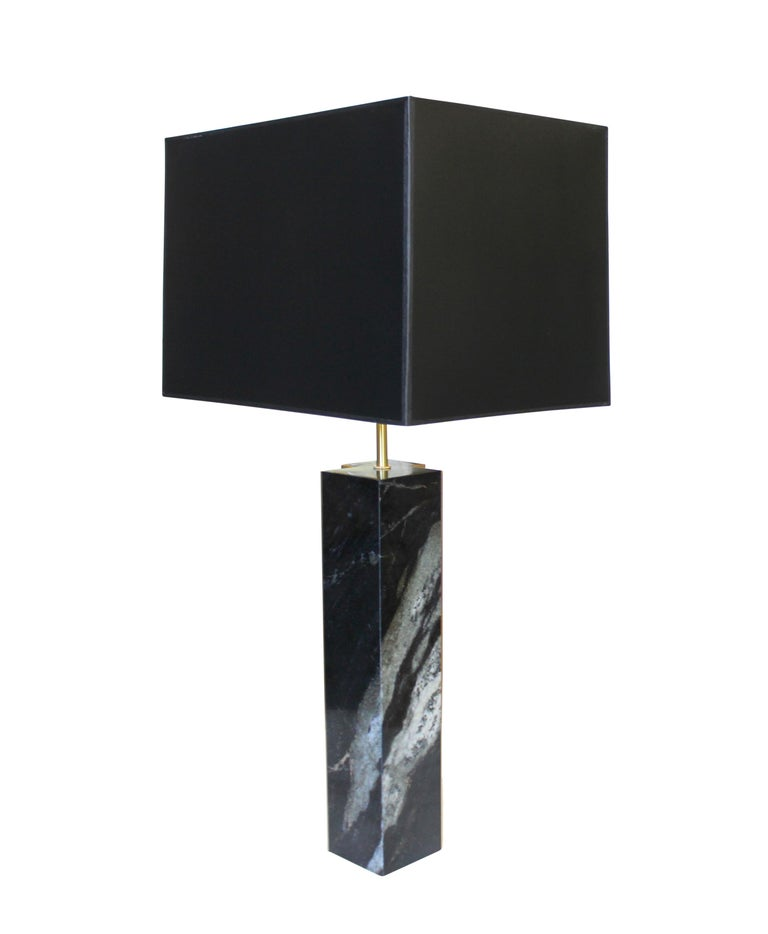 Black and white dalamata quartzite table lamp with bronze accents and black paper shade with gold interior.