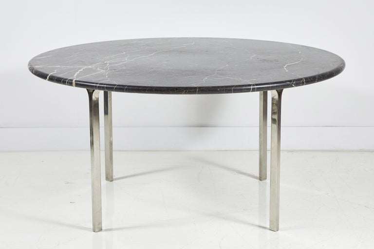 Round chrome dining table with heavy black marble top.