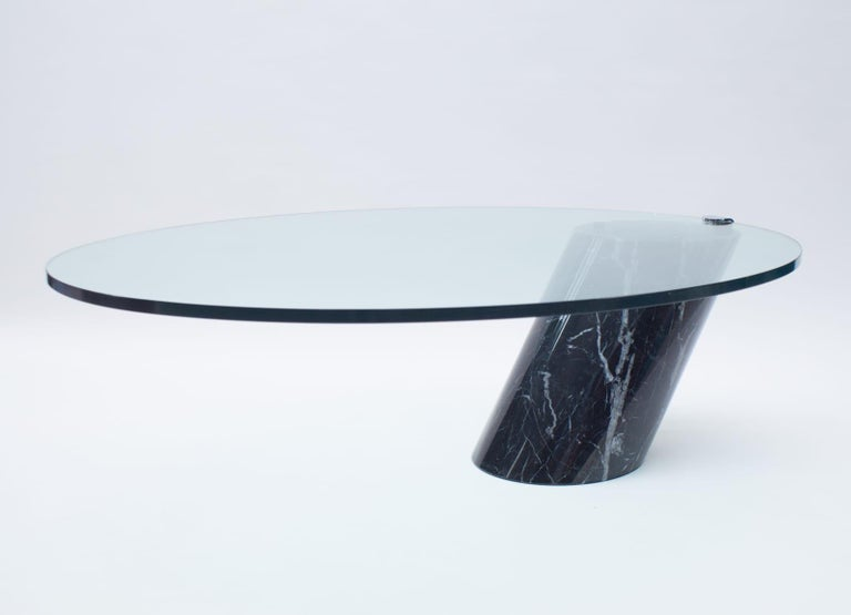 Black Italian marble with beautiful white veining.  Coffee table designed by Team Form for Ronald Schmitt in the 1970s. The base of this table is made from solid marble.   The thick oval glass top lays loose on the marble base only held in to