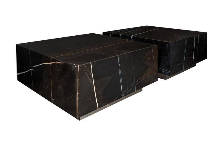 Black marble cocktail tables on bronze mirror bases.