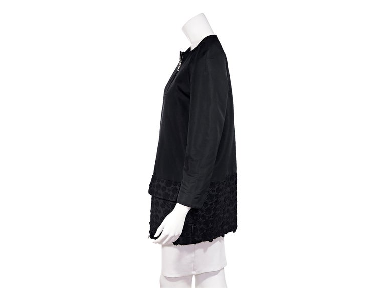 Product detail: Black cotton-shell coat by Moncler. Collarless. Cropped sleeves. Dual flap pockets at hips. Floral-embroidered at hem. Dual zip-front closure. Silver-tone hardware. Pair with a ruffled high-collar top to show off the neckline. The
