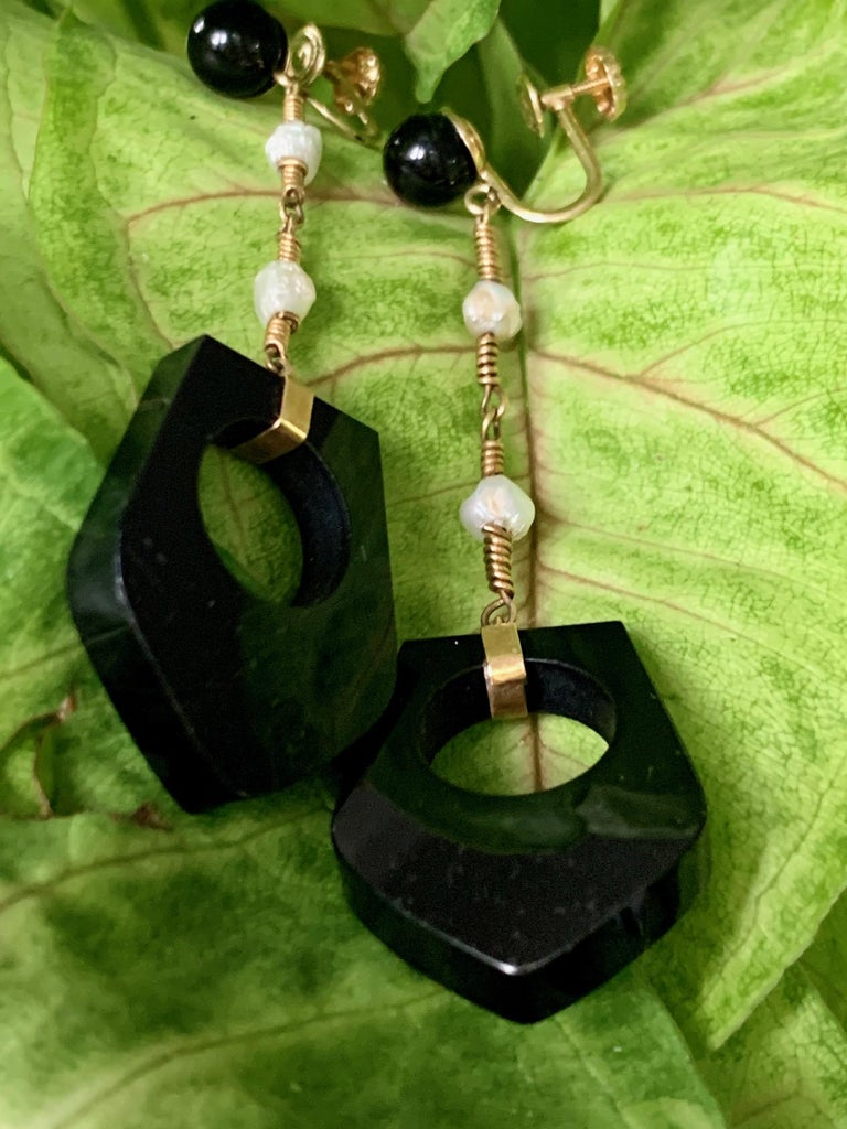 These fun and unique earrings feature a dangle of a uniquely shaped piece of black Onyx.  The Onyx hangs from a chain which has two fresh water Pearl accents.  The ear piece has a black Onyx bead.    Weight:  11.9 grams