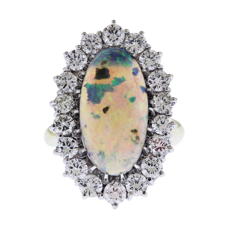 18K Yellow and White Two Tone Gold Ring with Black Opal center and Diamonds  Ring is entirely hand made from start to finish and features a stunning, incredible Black Opal center  Black Opal center is 20mm by 12mm Oval Cut  Surrounded by apprx. 3.50