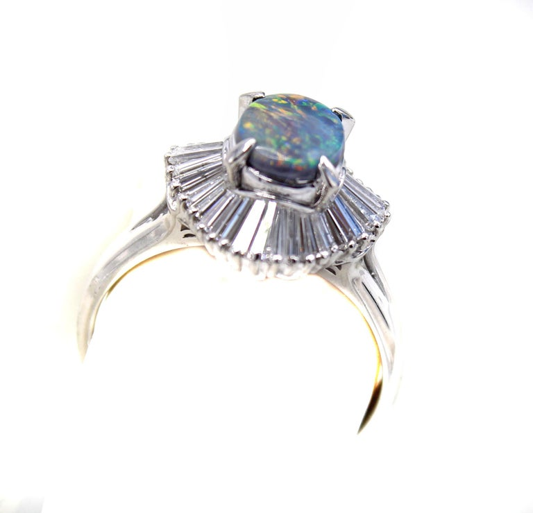 Beautifully designed and wonderfully hand-crafted this 1970s ring features an oval black opal surrounded by bright white tapered baguette cut diamonds. The black opal displays an amazing amount of red, along with blue, green and orange. The