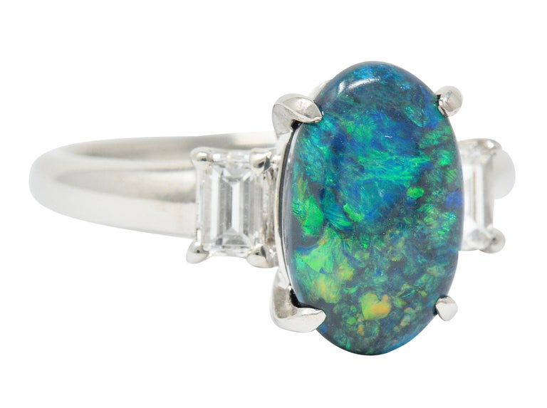 Centering an oval black opal cabochon measuring approximately 11.6 x 7.3 mm  Black in body color with strong blue, green, and yellow play-of-color  Flanked by rectangular step cut diamonds weighing 0.37 carat; F/G color with VS clarity  Inscribed