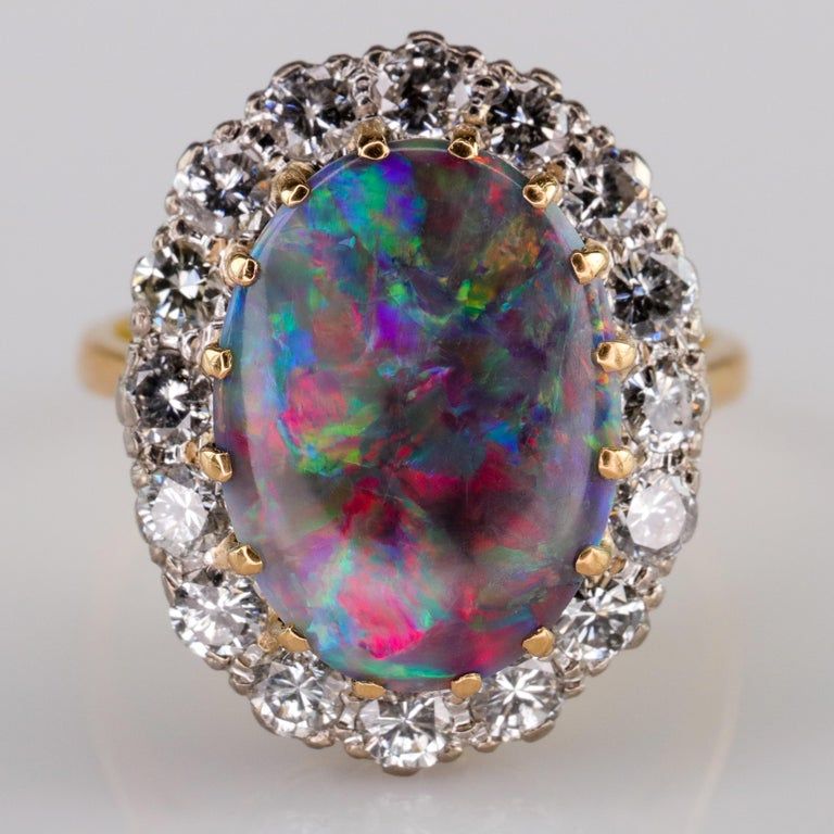 A brilliantly colorful 14.27 mm x 11 mm solid (not a doublet or triplet) black opal from Australia's famed Lightning Ridge is the breathtaking kaleidoscopic centerpiece of this English halo ring. Hand-crafted in rich 18k yellow gold, the black opal