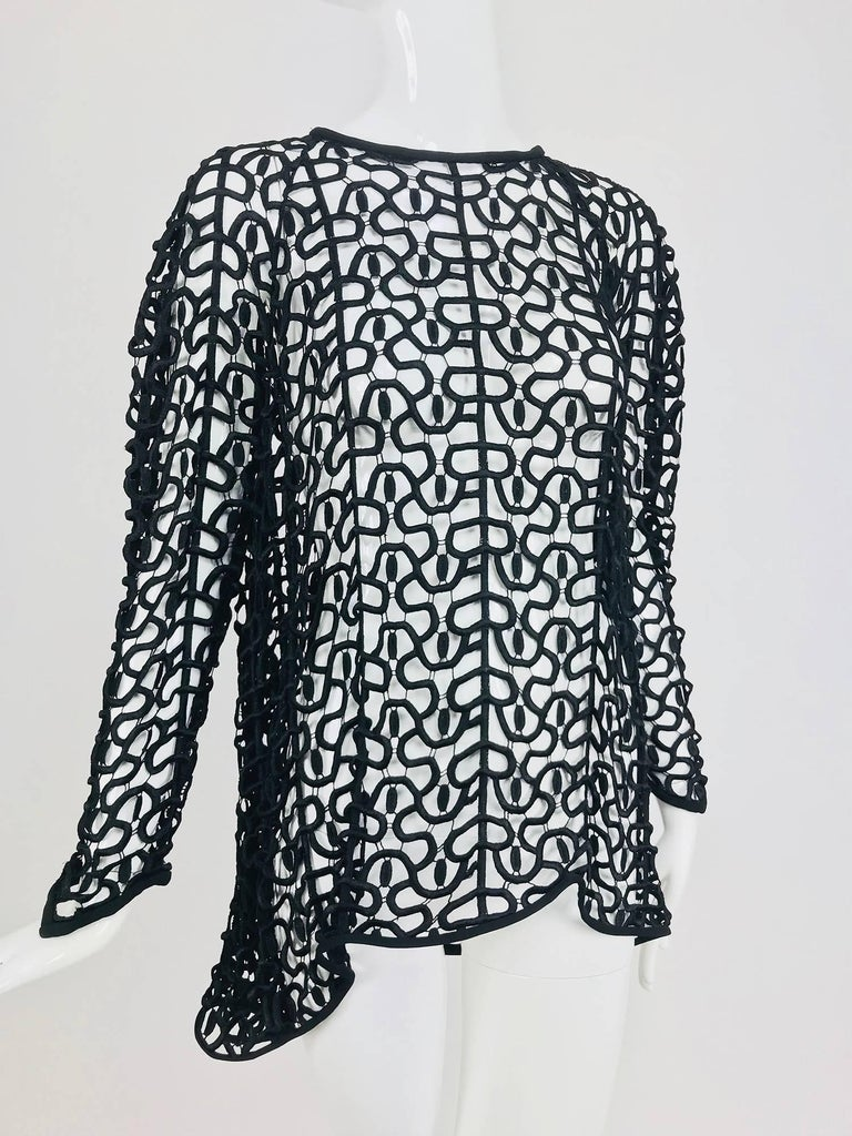 Black open work embroidered top with high low hem...Made like cut work lace of heavily embroidered thread with delicate connector threads facings of black crepe...Well made pull on top has long raglan sleeves that each end in points at the cuffs,