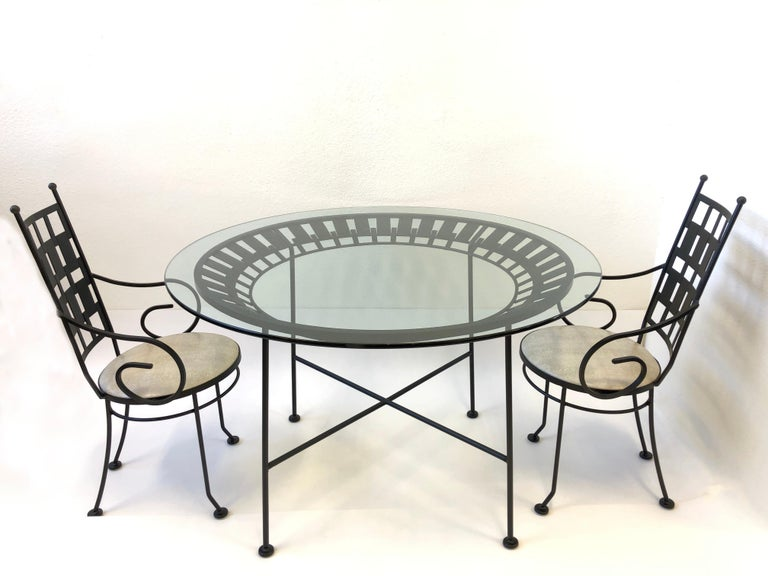"Glamorous high back armchair and table design by Arthur Unamoff in the 1960s. The set is constructed of steel that has been newly powder coated satin black, new 48"" diameter 1/2"" thick glass top and seats on chairs are newly recovered in a off-white"