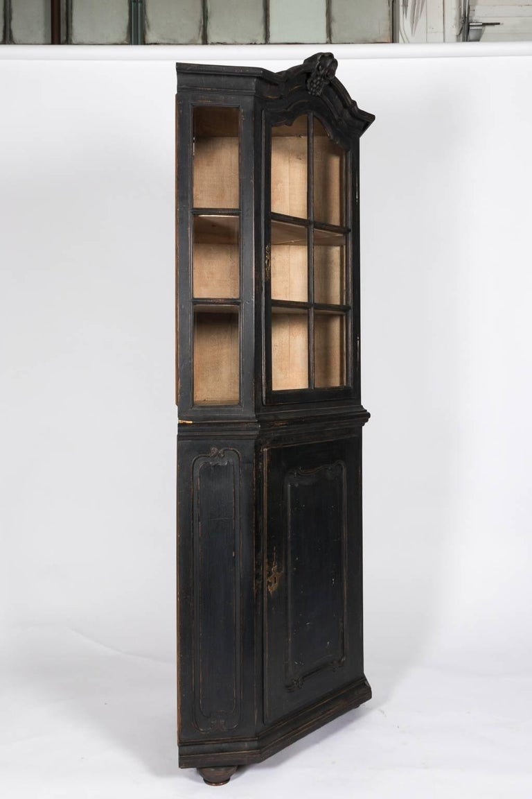 Black painted rococo style corner cabinet with glass fronts and a curved top circa late