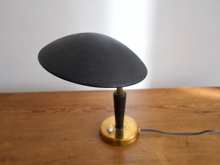 Small table lamp from the 1930s with adjustable black metal screen, brass base and rod and black painted wood detail. Manufactured and stamped by Nordiska Kompaniet. European plug.
