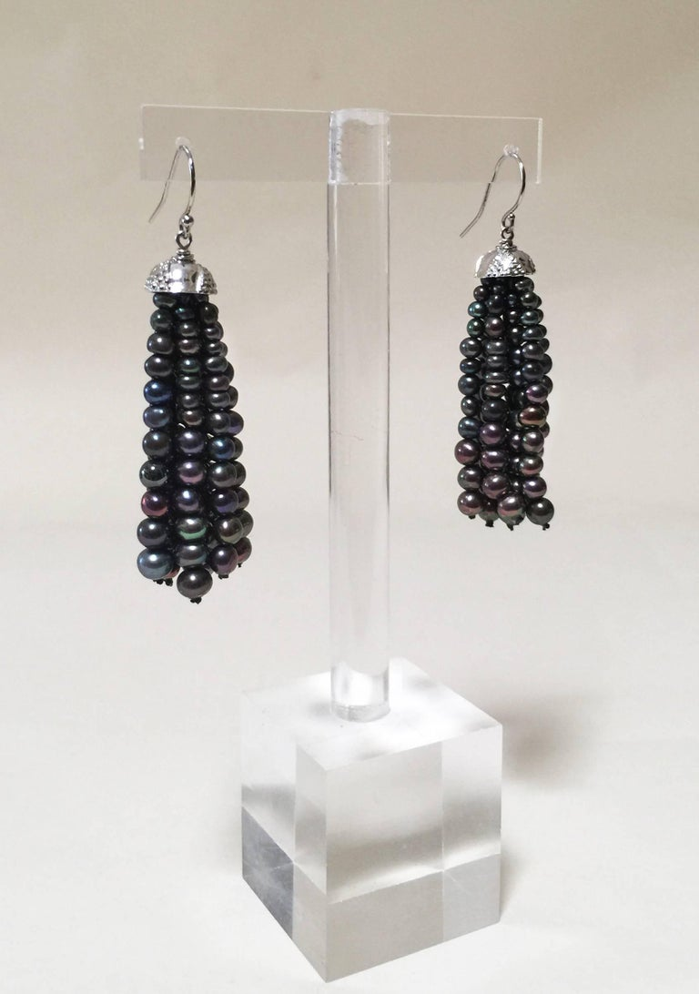At 2.5 inches long these black pearl tassel earrings gracefully framing the face. Each pearl was carefully chosen for its size, shape, and color to create a graduated look, giving off a classic elegance. The white gold plated silver cup is detailed