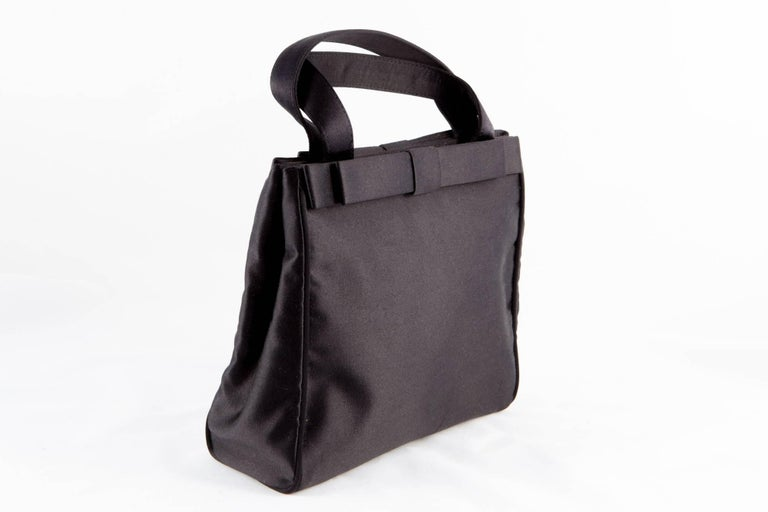 Black Prada satin evening small tote bag featuring black silk tie bow appliqué on both sides,  top handles,  an inside gold-tone logo plaque, a top magnetic closure, an internal zipped pocket, an internal slip pocket and a logo silk lining.  In