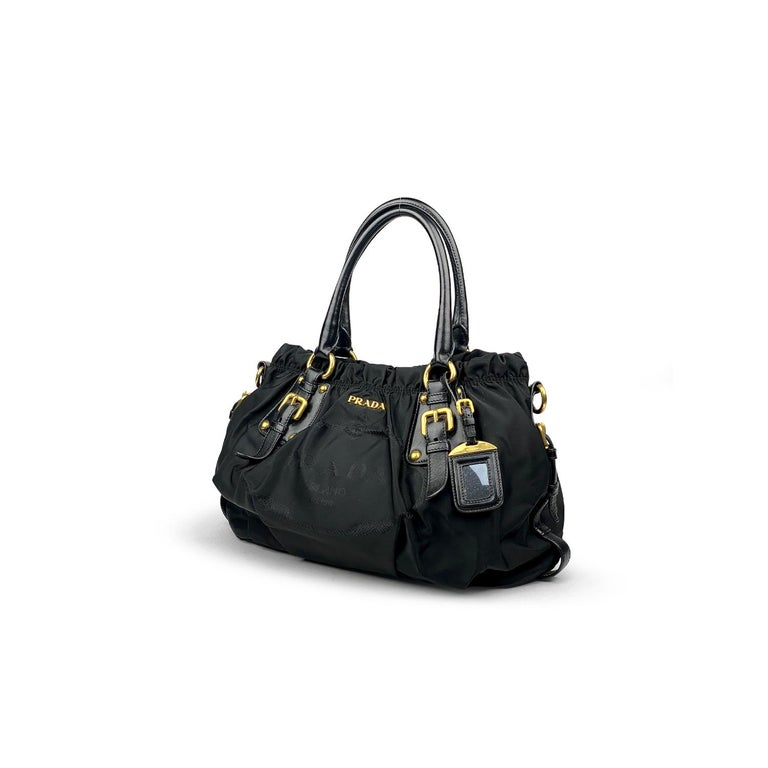 Black Tessuto nylon Prada satchel with   - Gold-tone hardware - Dual rolled handles - Black leather trim - Embroidered logo at front - Black logo jacquard lining, dual interior pockets; one with zip closure and snap closure at top  Overall Preloved