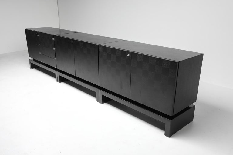 Brutalist sideboard consisting of three modular cabinets by De Coene, Belgium, 1970s. The ebonised oak door panels show a square geometric scene. One of the three cabinets has four drawers, the other two have identical shelving.