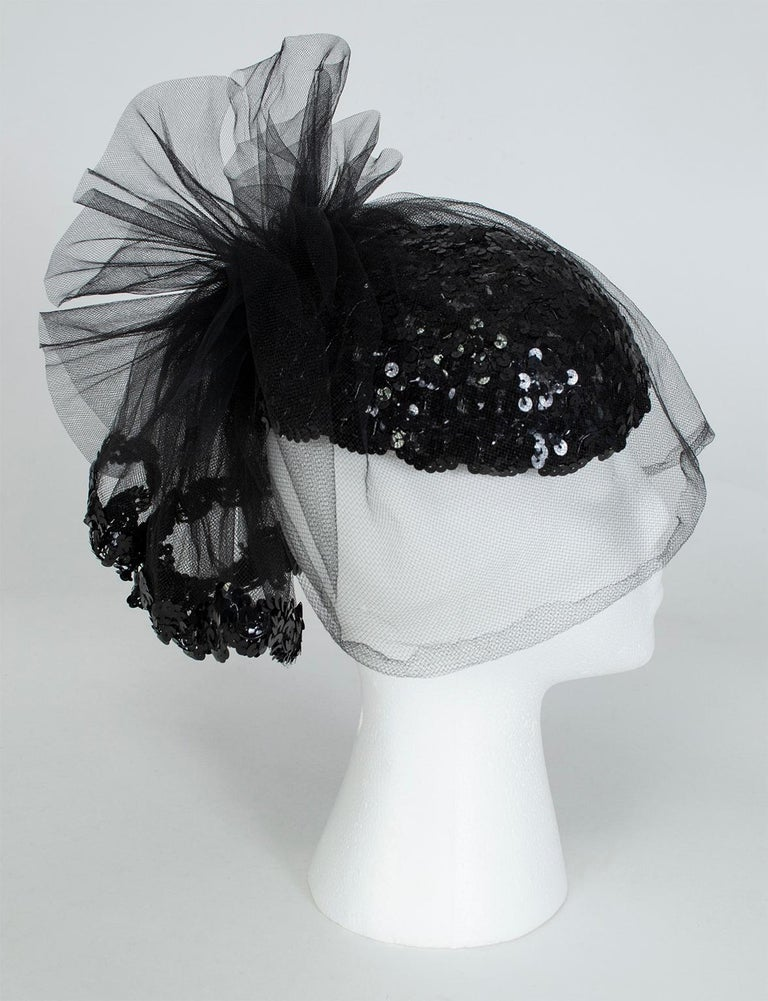 A knockout accessory for New Years Eve or a black tie event, this cocktail hat is as petite as a fascinator but packs the punch of a wide brim. Both glitzy and understated, it balances a glittering sequin skull cap with an alluring cage veil for an