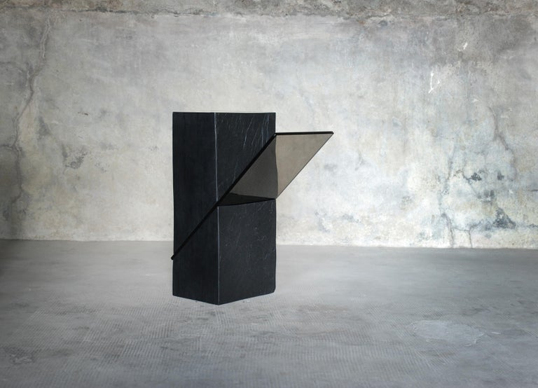Black slate gue´ridon - Averti. Materials: Tre´laze´ black slate and grey smoked glass. Dimensions: 50 x 25 x 18 cm.  Edition of eight. Signed and numbered.