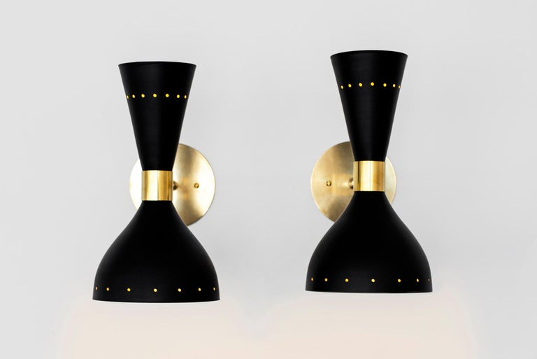 Great pair of Italian metal sconces in the style of Stilnovo, newly produced in Italy.  Black metal shade with brass detailing and back-plate. Sconces shine both up and down light. Wired to American standards.