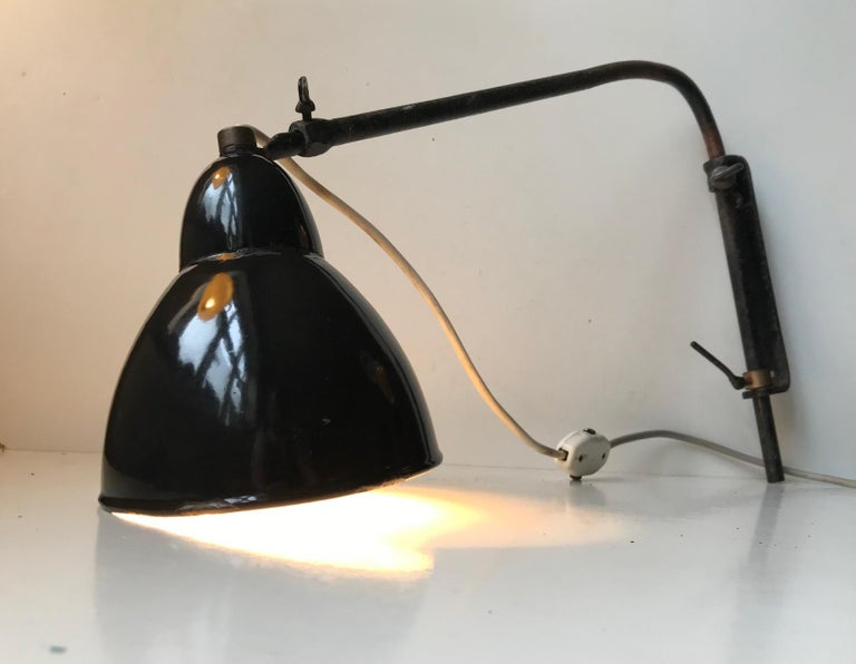 Extendable wall light with side-side, swing arm, adjustable mounts. This light has an Industrial provenance an it came out of a metal workshop in Leipzig Germany where it had been hanging since the 1930s. It has a reach/dept that are adjustable up
