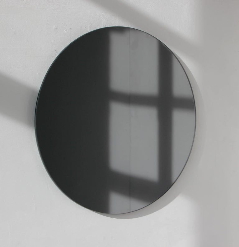 Delightful crafted black tinted round mirror frameless with a floating effect. Design and hand-crafted in London UK.   Supplied fully fitted with a specialist hanging system for an easy installation.  Measures: Diameter 50cm/19.7''  Also available