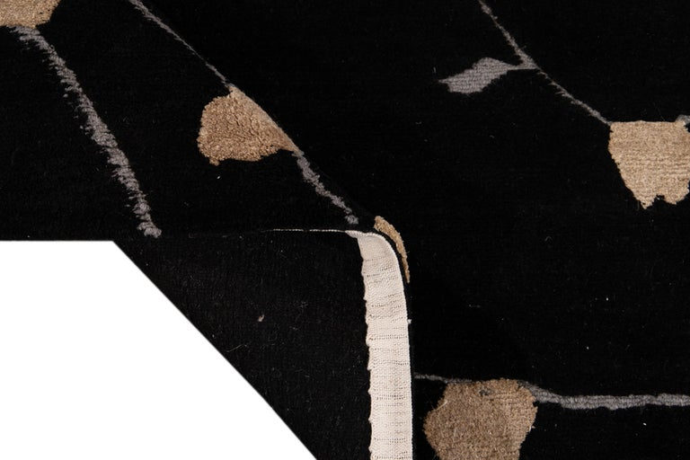 Beautiful Transitional Tibetan hand knotted wool rug with a black field. This Tibetan rug has accents of gray and beige in a gorgeous all-over Botanical Floral design.  This rug measures: 9' x 12'.