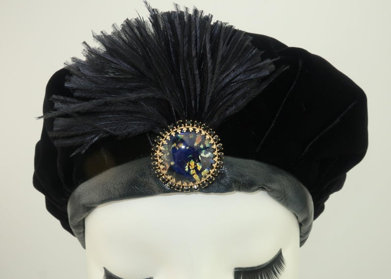 This 1980's hat is loaded with a 1930's personality.  The lush black velvet body is lined with faille fabric and trimmed in supple leather.  The little detail that takes this look from practical to perfect is the reverse blue & gold painted glass