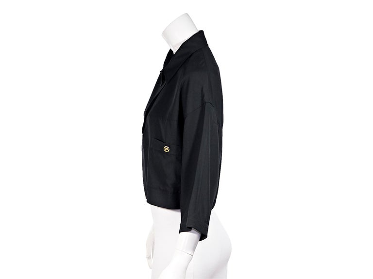 Product details:  Vintage black linen crop top by Chanel Boutique. Pointed collar.  Cropped sleeves.  Partially concealed button-front closure. Dual pockets at front. Laser-cut logo buttons. Gold-tone hardware. Style with high-waist black jeans.
