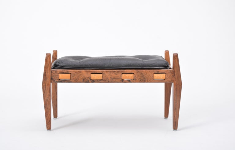 This ottoman or foot stool was designed and produced in the 1960s in Brazil. It is attributed to Sergio Rodrigues. The structure is made of rosewood. Four cone- shaped legs with leather straps, cushion padded in black buttoned leather. The leather