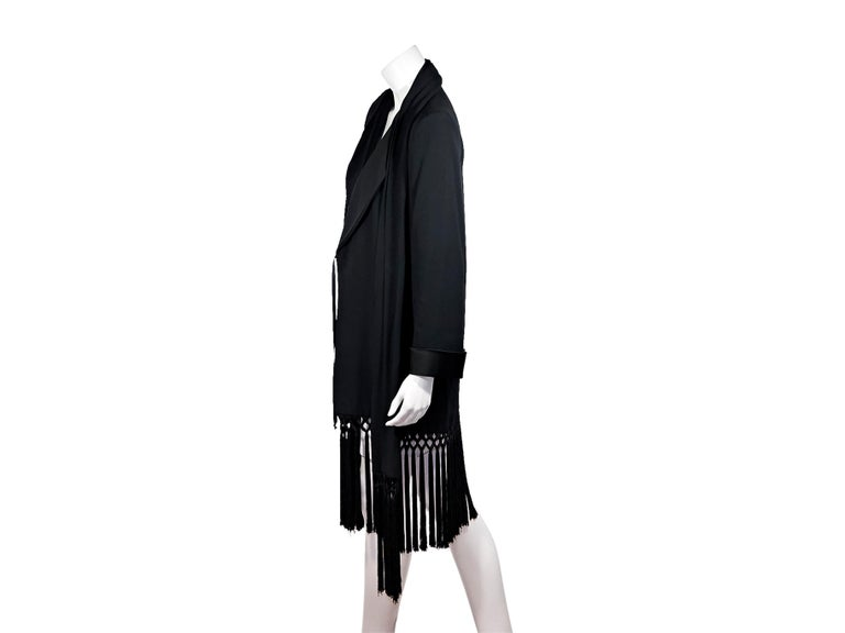 Product details:  Vintage black gabardine jacket by Yves Saint Laurent. Trimmed with black fringe.  Shawl collar. Cropped sleeves.  Concealed front closure. Label size FR 34. Style the oversized fit with slim-leg ankle pants. 38