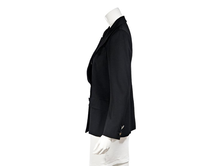 Product details:  Vintage black double-breasted wool blazer by Yves Saint Laurent Rive Gauche.  Peak lapel.  Long sleeves.  Double-breasted button-front closure.  Two-button detail at cuffs.  Besom chest pocket.  Waist flap pockets.  Label size FR