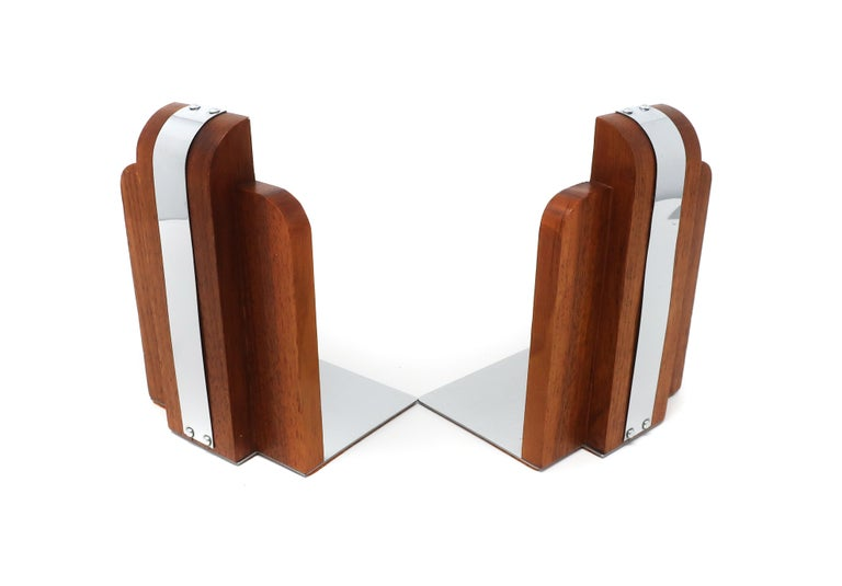 "A pair of art deco or early mid-century modern bookends. Made from walnut with a chrome stripe and chrome horizontal support. Felt on underside with sticker (reads ""Solid Black Walnut"") but no maker's mark. In excellent vintage condition with wear"