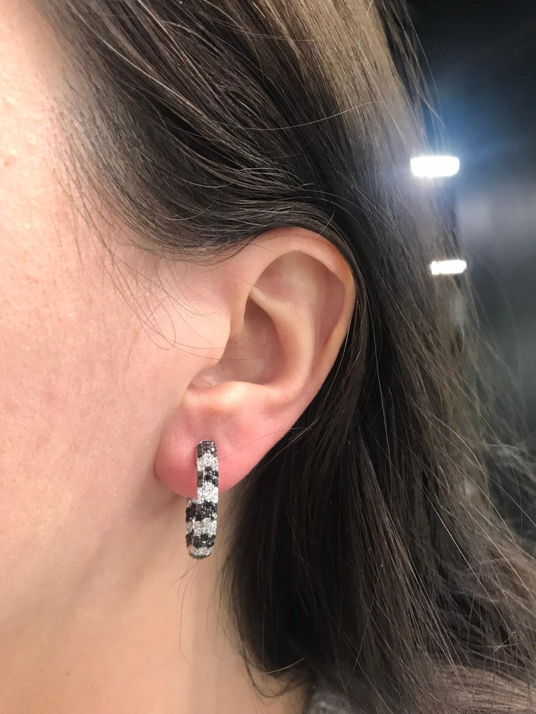 18K White Gold hoop earrings featuring 112 black diamonds weighing 2.70 carats and 84 round brilliants weighing 1.60 carats. Color G-H Clarity SI
