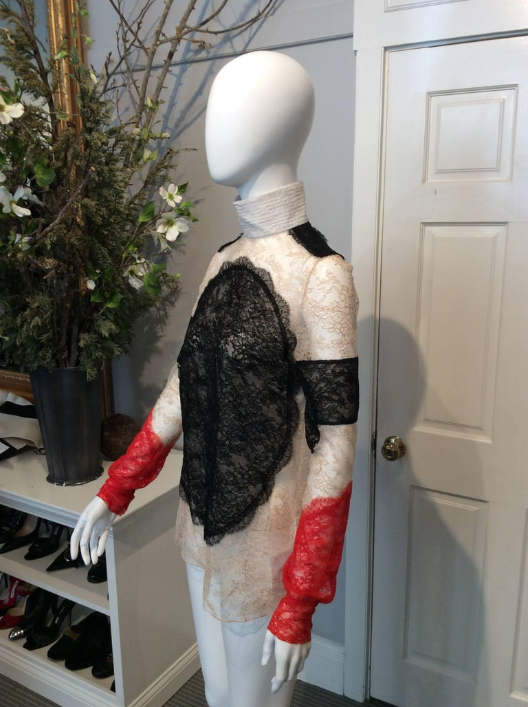 Black, red, nude lace Givenchy semi-sheer long-sleeve top with ivory high-collar. Zipper with hook and eye closure at back of neck. Three red fabric covered buttons located on cuff.   Sizing: Fr36, Us4  Fabric content: 70% nylon, 30% viscose