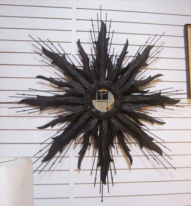 American, mid-20th century. Blackened Brutalist style polychromed steel wall-hanging starburst mirror, with a central, round mirrored panel, bordered with shaped wire scrolls, surrounded by hammered torch-cut sunrays and wire rods.